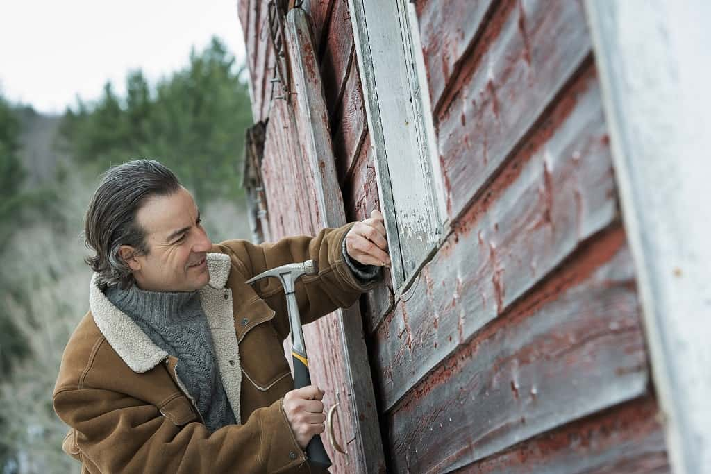 man with hammer fixing the window of a barn